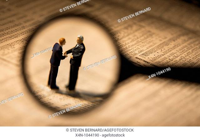 Miniature businessmen, seen through magnifying glass, shake hands while sstanding on financial newspaper