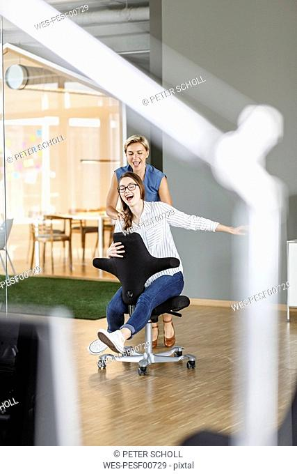 Playful employee pushing colleague on office chair