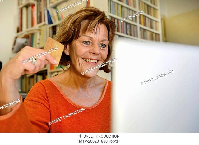 Senior woman shopping online with credit card, smiling