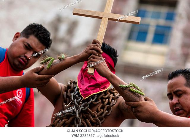 A hooded Catholic penitent, wearing chains and cactus spines stuck to his body, raises a wooden cross during the Holy week procession in Atlixco, Mexico