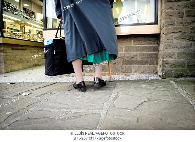 Back view of an unrecognizable old lady wearing a bag and a stick looking at shop window. Skipton, Yorkshire, England, UK