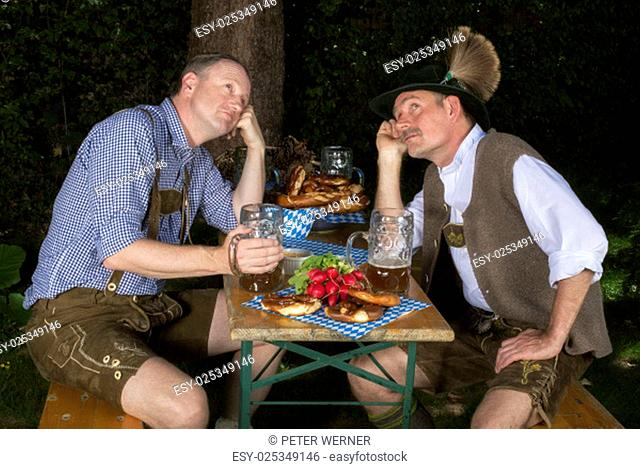 two bavarian men sitting in a park ,drinking beer and looking tired