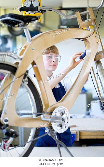 Female high school student assembling bicycle in woodworking class