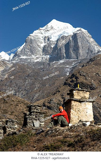 A trekker stops beside a chorten to admire the views on the way to Everest Base Camp with views of Taboche in the distance, Khumbu Region, Himalayas, Nepal