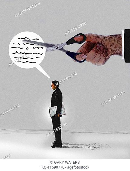 Large hand with scissors cutting words in speech bubble of businessman