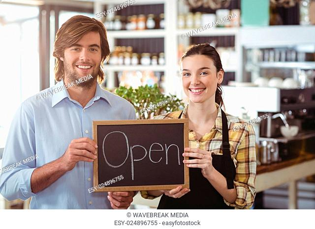 Portrait of man and waitress holding chalkboard with open sign