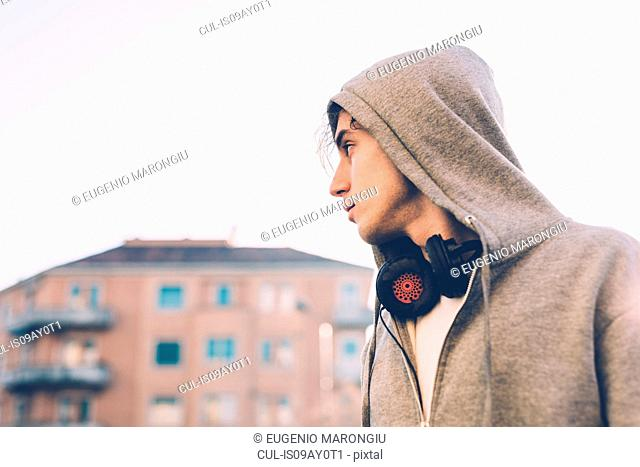 Portrait of man wearing hooded top and headphones looking away