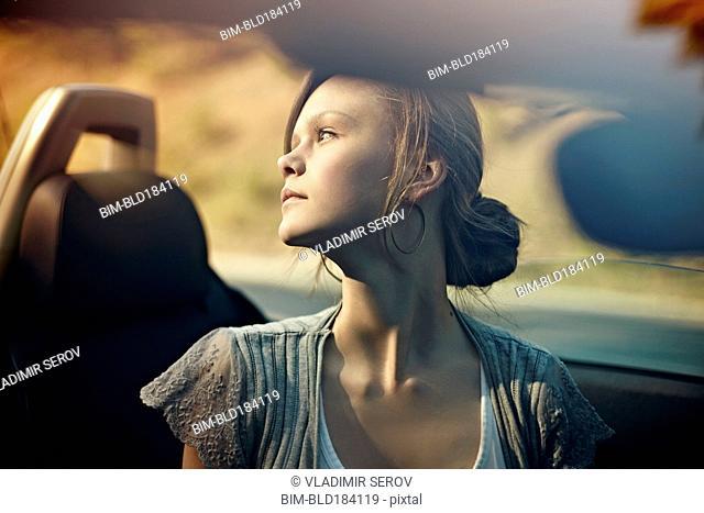 Caucasian teenage girl sitting in convertible