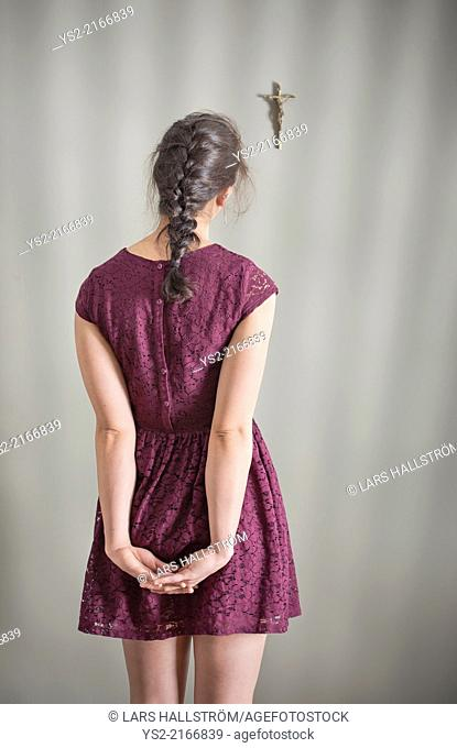 Back view of woman looking at crucifix hanging on wall