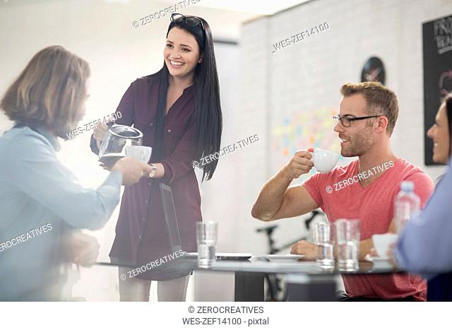 Employee pouring coffee into cup for colleague