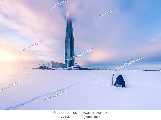 "SAINT PETERSBURG. RUSSIA - January 27 2019. Skyscraper """"Lakhta center"""" (Gazprom headquarters) twilight. Frozen sea side view against sunset sky"