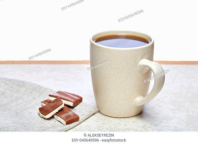 White ceramic porcelain coffeecup with a couple of chocolate pieces on white cotton napkin on light concrete background, top view. Pleasure coffetime
