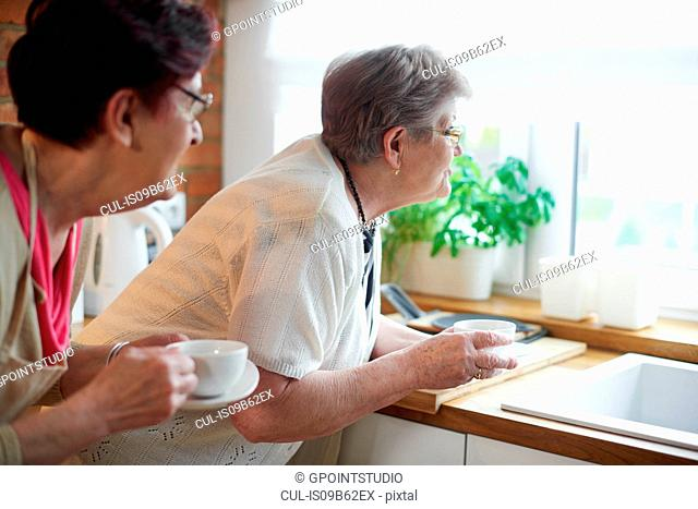 Senior adult women drinking coffee and peering out of window