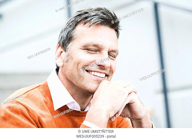Businessman wearing orange sweater, portrait