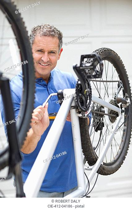 Man working on bicycle in driveway