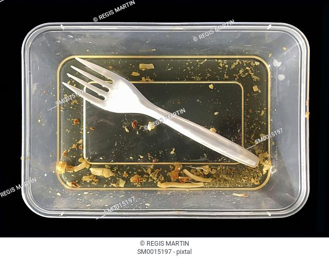 Greasy take away food container and plastic fork, after a meal