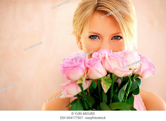Portrait of a pretty young woman holding a bunch of pink roses
