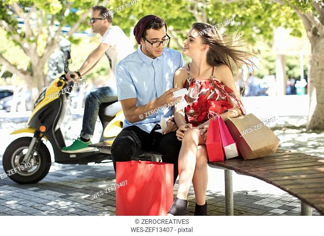 Man checking shopping bill with girlfriend looking at him