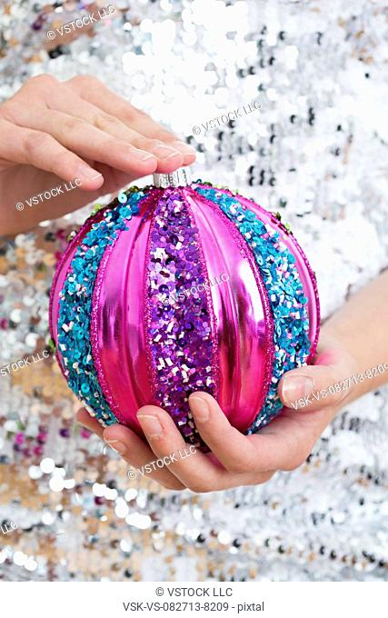 Mid section of teenage girl (14-15) holding Christmas ornament