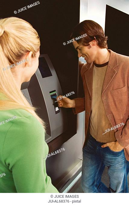 Couple using an automated banking machine
