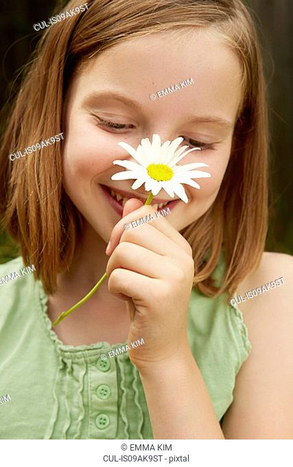 Portrait of girl in garden holding up daisy