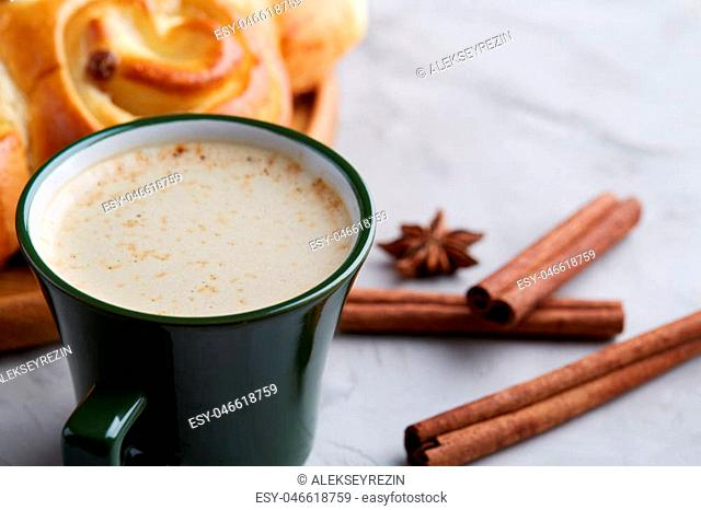 Festive still life with homemade rose bread with raisins, cup of coffee, anise and cinnamon over white textured background, close-up, top view
