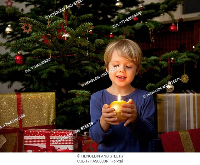 boy holding candle at christmas