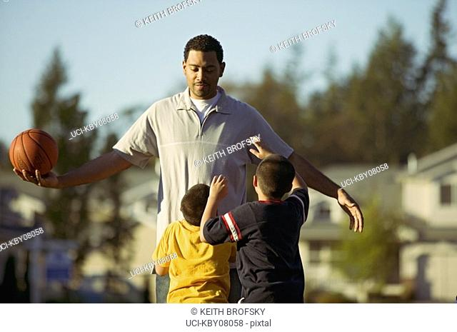 African father and sons playing basketball