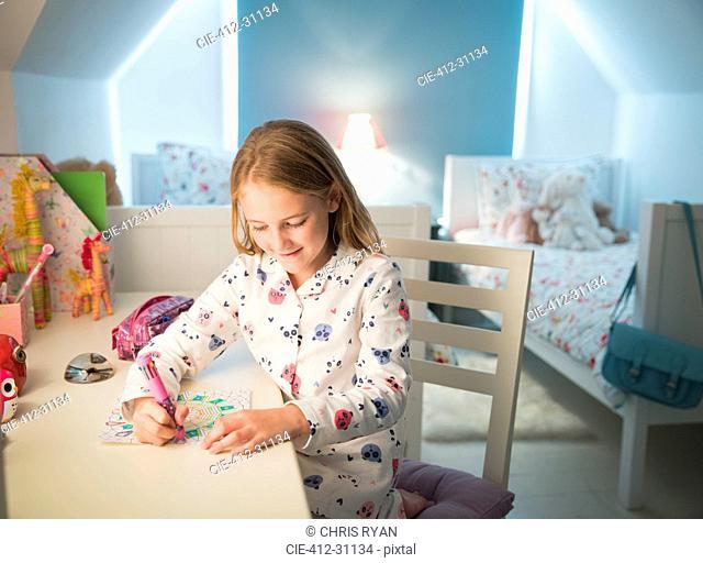Girl in pajamas coloring at desk in bedroom