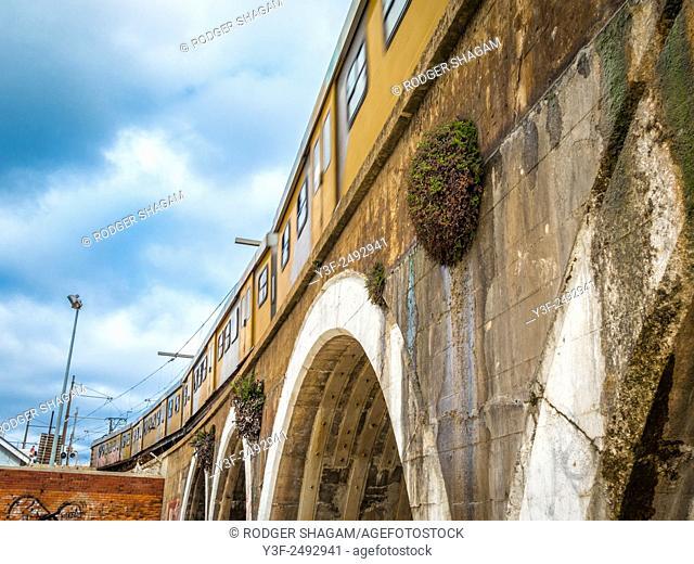 Arches of an old railway bridge at Kalk Bay Harbour, Cape Town, South Africa. A train runs overhead