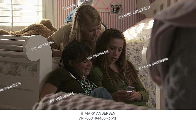 Three young girls sending a text message