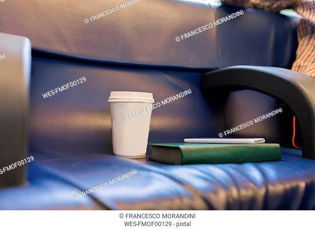 Coffee to go, book and smartphone on seat of a train