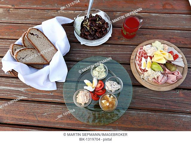 Hearty snack, bread and a plate with a variety of spreads, Brettljause, a plate with cold cuts, Styrian scarlet runner beans and a glass of Schilcher Sturm