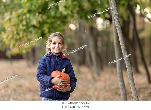 Portrait of smiling girl holding pumpkin in forest