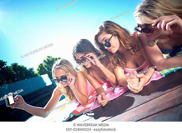 Group of friends taking selfie near poolside