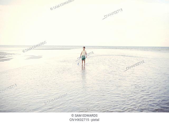 Portrait boy holding shove in ocean surf on overcast summer beach