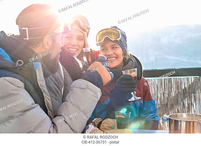 Smiling skier friends drinking cocktails apres-ski