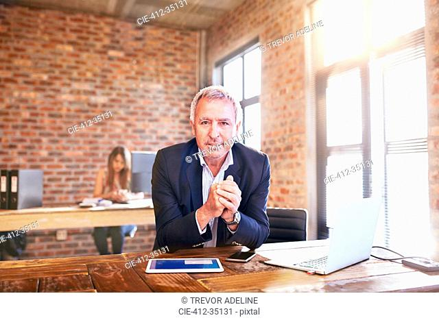 Portrait confident businessman with digital tablet and laptop working in office