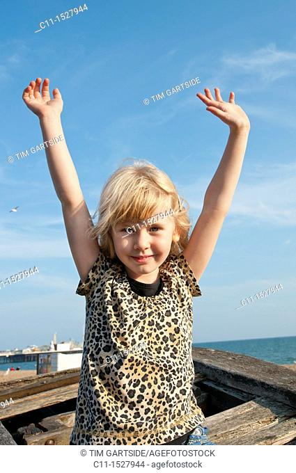 young girl smiling and waving,Brighton, East sussex, England, Europe, UK
