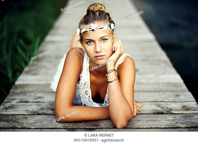 Young woman in white dress on a footbridge