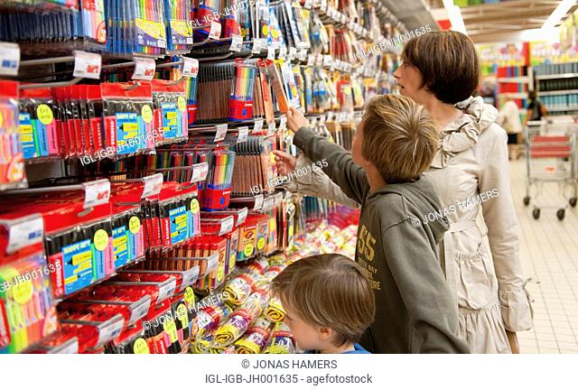A mother and her two children shopping and buying elementary school supplies in a supermarket