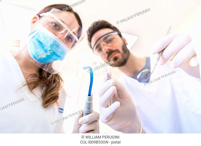 Patient viewpoint of male dentist and dental nurse holding dental equipment