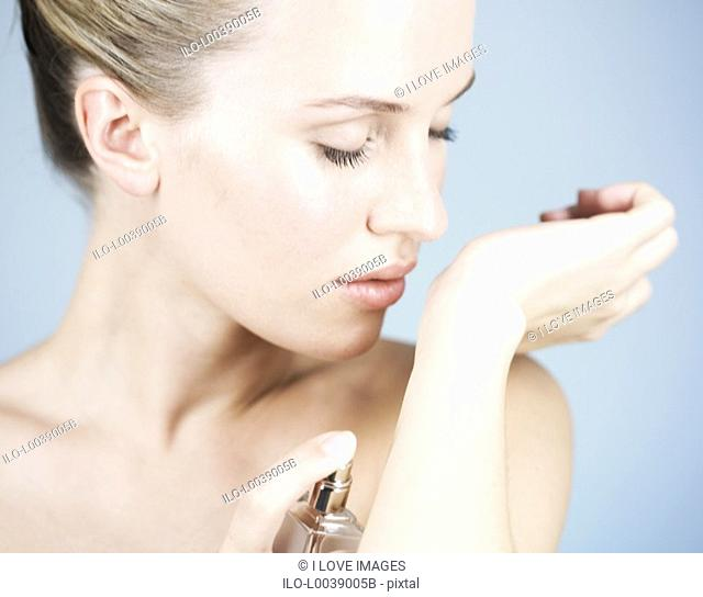 A young woman applying perfume