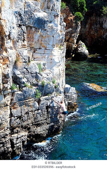 climber is climbing up on cliffs over the sea