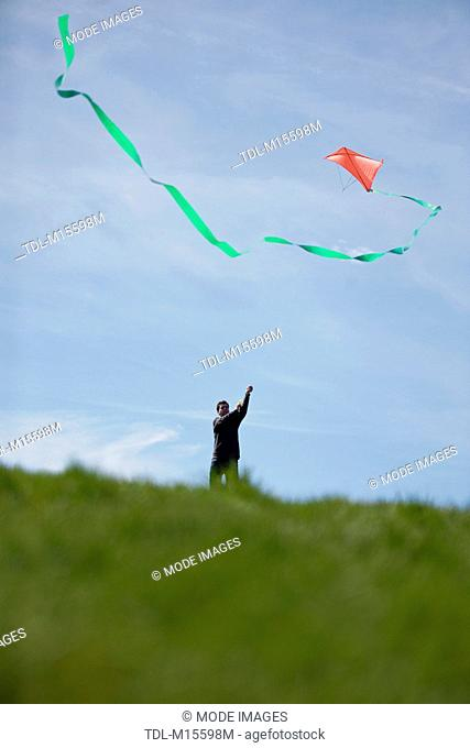 A man flying a red kite