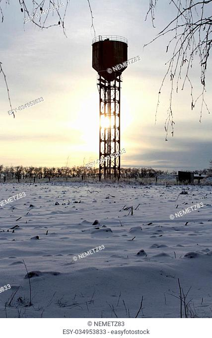 The old water tower in the middle of snow-covered field against the sunset