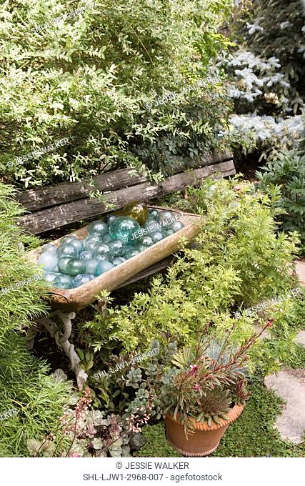 GARDEN: Park bench almost covered by shrubs, wooden bowl filled with blue glass balls, terra cotta pot