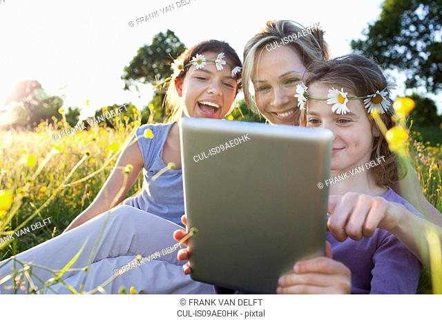 Mother and daughters in field using digital tablet