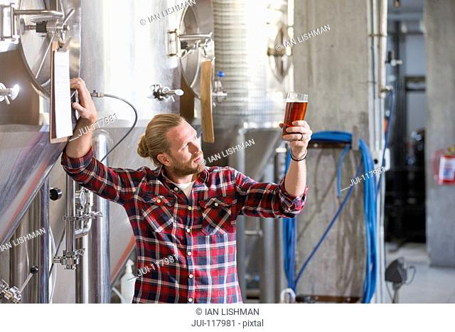 Male Brewery Worker Quality Checking Beer Sample