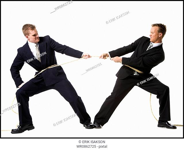 Business people engaged in a tug of war contest